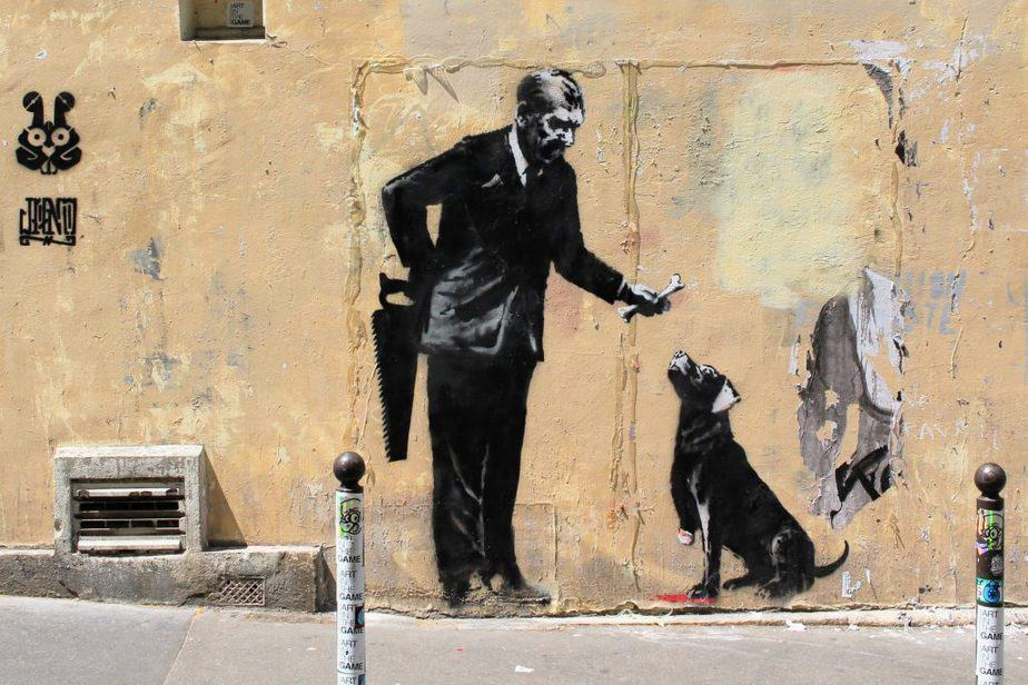 "Banksy's stencil ""businessman give a bone to a three-legged dog"", in front of the sorbonne university in Paris"